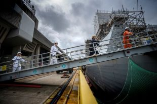 BAE employees walk up gangplank to naval ship with 2m distance between them