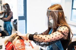 Salon owner Melissa Timperley wears PPE whilst givings client hair foils