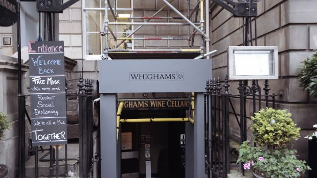 Exterior of Whighams Wine Cellars in Edinburgh with blackboard outling social distancing rules