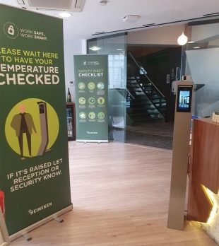 COVID-19 safety advice and temperature checking station at reception of Heineken London office building